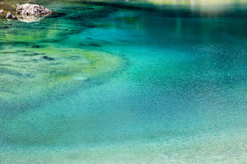 Different colors of a lake in the Dolomites in South Tyrol, Italy
