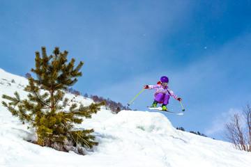 Little girl skier in a jump