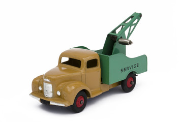 Vintage green and brown toy towing truck. Isolated against a white background.