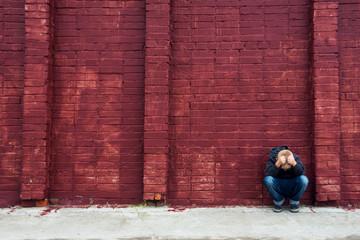 Depressed child and brick wall