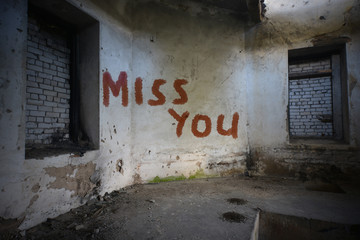 text miss you on the dirty old wall in an abandoned ruined house