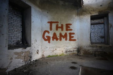 text the game on the dirty old wall in an abandoned ruined house