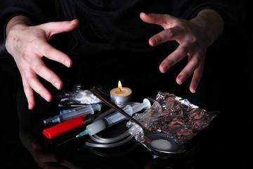 Drug addict with syringe on black background