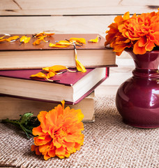 Flowers. Beautiful yellow chrysanthemum in a vintage vase. Old books on a wooden background.