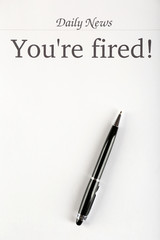 Message You're Fired on sheet of paper with pen, closeup