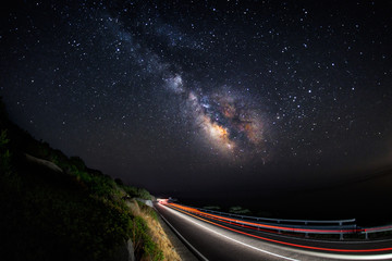 Light trails on the road with the milky way galaxy on the sky (horizontal)