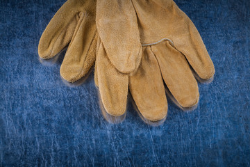 Close up image of leather brown protective gloves on scratched m
