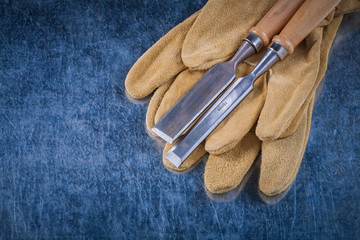 Firmer chisels and leather safety gloves on scratched metallic s