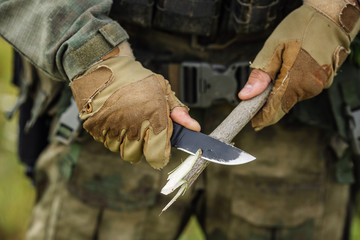 soldier with a knife cut a wooden stick