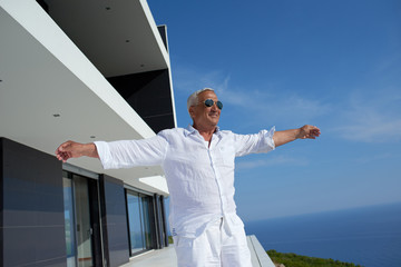 senior man in front of modern home