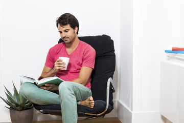 Man Sitting on Chair with Book and a Drink