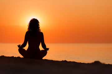Silhouette of woman in yoga lotus meditation position front to s