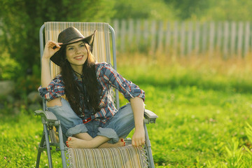 girl in a wide hat resting on a sun lounger on the ranch