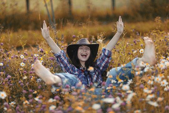 Happy American woman in a cowboy hat field wild flowers