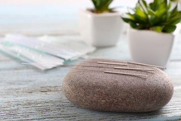 Acupuncture needles with spa stone on wooden table, closeup
