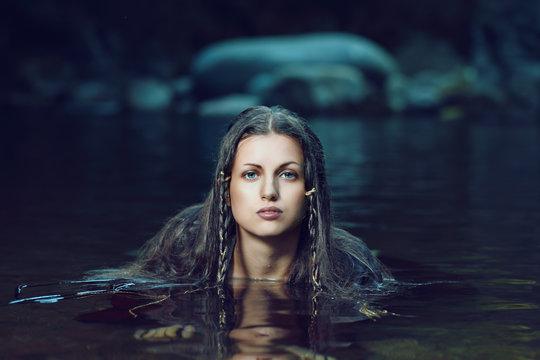 Beautiful woman in dark water stream
