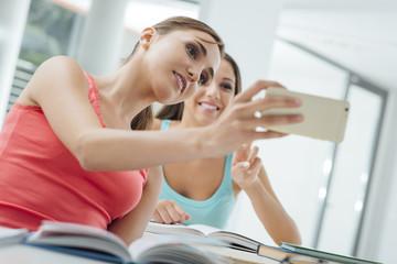 Smiling girls taking selfies at school
