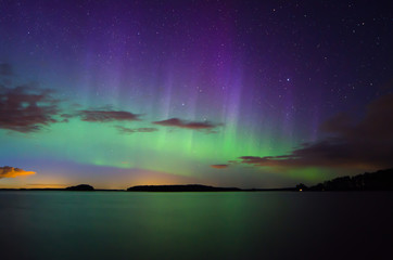 Northern lights (Aurora borealis) over calm lake in Sweden