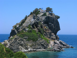 Church of Agios Ioannis at Skopelos island on cliff top in sea. Greece.