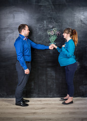 husband giving bouquet to pregnant wife against chalk drawing