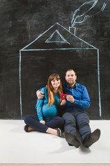 Happy family posing against house drawn on chalkboard