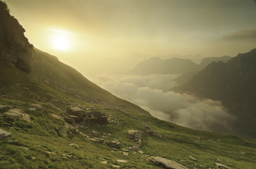 Fotomurales - Cloudy sunrise in the mountains of Ticino, Switzerland.