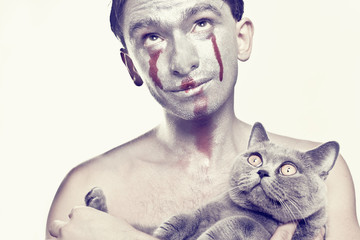 Man with silver makeup on his face and cat in  hands