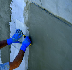 worker placing mesh sheet plastic on concrete wall with cement mortar and resins