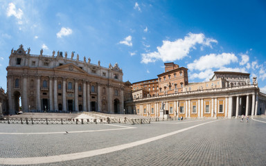 A super-wide fish-eye view of the popular tourist attraction St. Peter's Square in the Vatican City with the Basilica and Popes palace creating a background to the tourists and pilgrims.