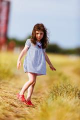 girl in a striped dress walking on the meadow