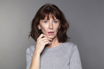 unhappy mature woman with brown hair and grey sweater thinking,looking concerned or questioning