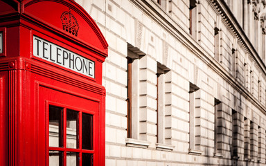 London telephone box. Traditional old-style UK red phone box set against a beige government building in central London.