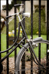 Locked bicycle. An old fashioned bicycle locked to some railings.