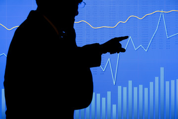 A man in silhouette points to a section of a stock chart graph on a large LCD screen. Could also be a scientific chart.