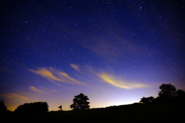 Starry Night Scene with Light Pollution Reflecting off Whispy Clouds in the Countryside