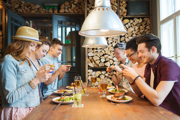 happy friends with smartphones picturing food