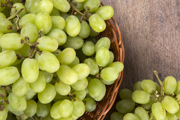 Green grapes in a basket over a wooden surface on a grape field