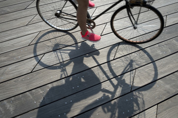 Shadow of cyclist riding across weathered smooth wood plank boardwalk background textured with modern angular lines