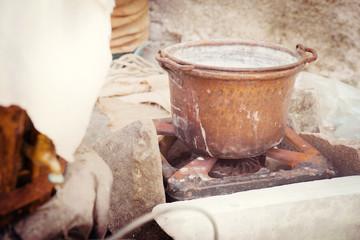 Antique copper pot boiling on a kitchen iron