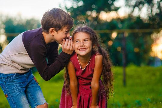 Teen boy whispering secret gossip girl child's ear to the street