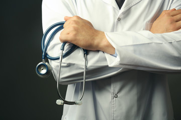 Male doctor holding stethoscope on gray background