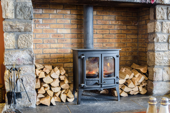 Wood Burning Stove in a Brick Fireplace