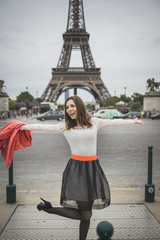 Happy young woman jumps near eifel tower Paris