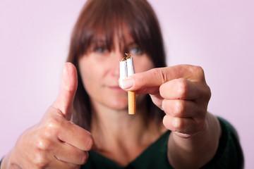 Frau hält zerbrochen Zigarette und den Daumen nach oben dazu