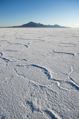 Dramatic white desert background of textured salt formations with rugged mountain range on the horizon