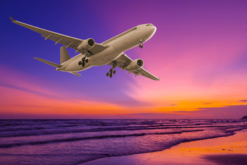 Commercial airplane flying above the sea at sunset