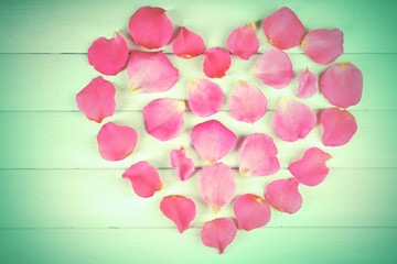 Heart of rose petals on wooden background