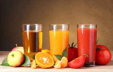 Three glasses of juice. Three glasses of juice, a glass with apple juice, a glass with orange juice, a glass with tomato juice. Stand nearby. Nearby apples oranges and tomatoes lie.