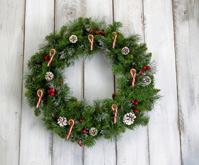 Christmas wreath with decorations on rustic white wooden boards