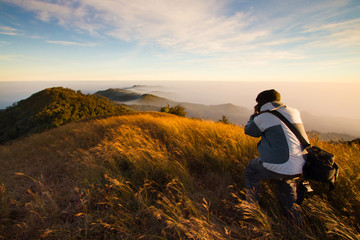 Photographer on high mountain in the morning at Thailand.